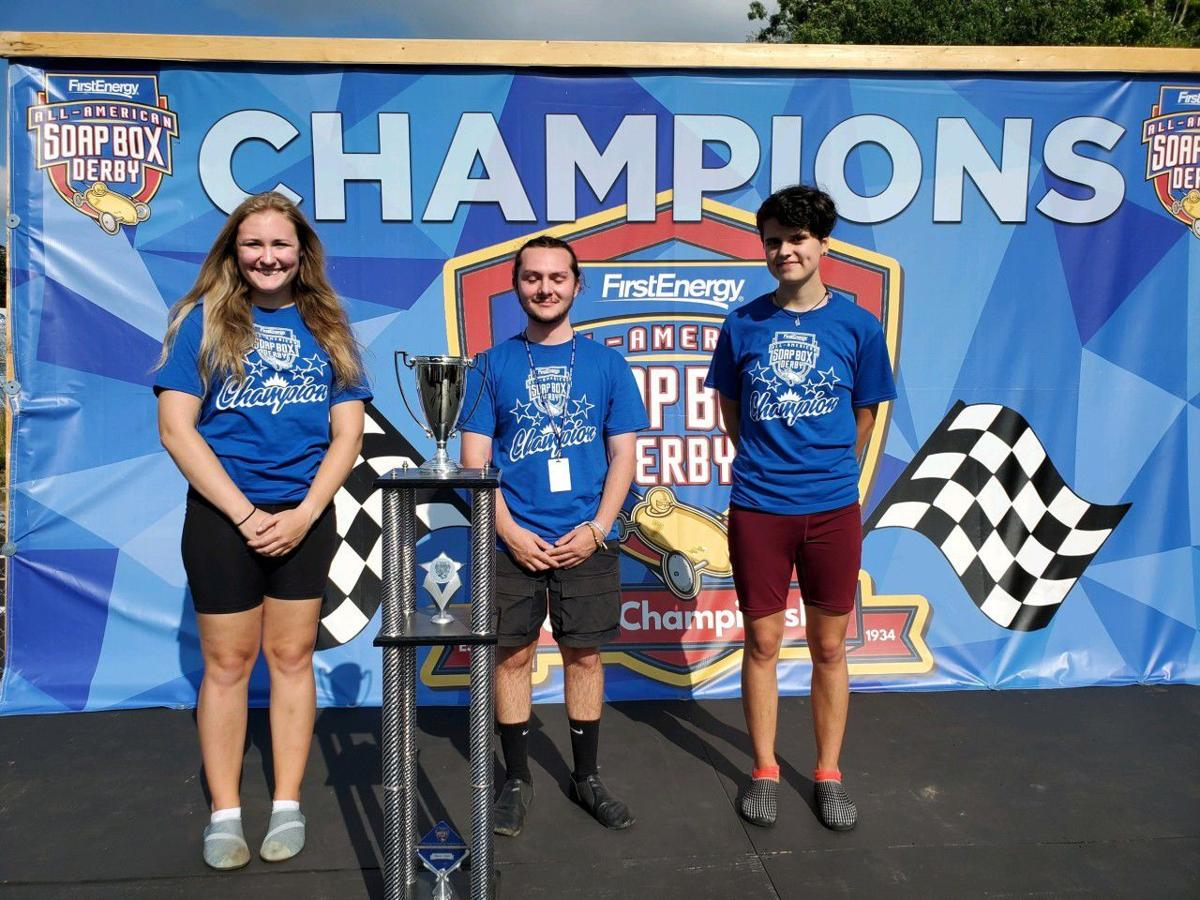 Ronan Johnson, middle, poses with his first-place trophy after winning the Rally Masters 3-Lane Challenge the 83rd All-American Soap Box Derby in Akron, Ohio.